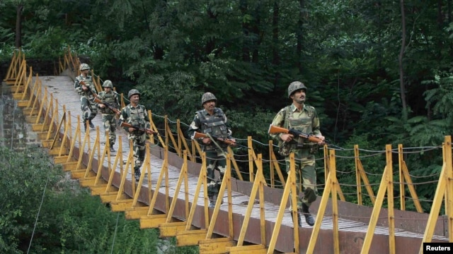 Indian Border Security Force (BSF) soldiers patrol a footbridge built over a stream near the Line of Control (LoC), a cease-fire line dividing Kashmir between India and Pakistan, in August.