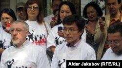"""Журналисты и правозащитники сидят в футболках с логотипом акции """"Вместе мы сильнее"""". Алматы, 8 сентября 2010 года."""