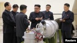 Кем Чен Ын (в центре) дает указания о развитии ядерной программы. Фото официально распространено в КНДР 3 сентября 2017 года.