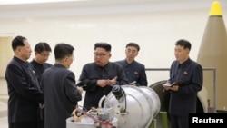 Солтүстік Корея басшысы Ким Чен Ын (ортада) ядролық бағдарламаны дамыту туралы айтып тұр. Пхеньян 2017 жылғы қыркүйектің 3-і күні таратқан ресми сурет.