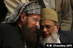FILE: Pakistani religious cleric Samiul Haq, left, talks with Syed Munawar Hasan, the head of the Jamaat-e Islami party in Lahore (2014).