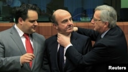 Spanish Economy Minister Luis de Guindos (center) jokes with Luxembourg Prime Minister and then-Eurogroup Chairman Jean-Claude Juncker (right) at a meeting in March 2012.