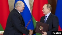 Russia - Russian President Vladimir Putin (R) exchanges documents with his Belarussian counterpart Alexander Lukashenko during a signing ceremony at the Kremlin in Moscow, Russia December 15, 2015