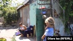 Анна Гайдукова и ее дочь во дворе дома, который семья арендует в микрорайоне Кайнарбулак. Шымкент, 1 августа 2017 года.