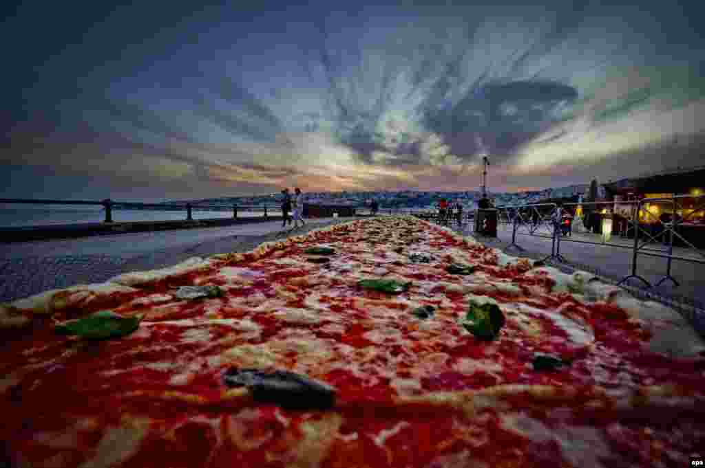 A general view of a Neapolitan pizza made to break the world record for the longest pizza ever made. The 41-centimeter-wide pizza stretches for 2 kilometers along Naples' waterfront. (epa/Ciro Fusco)