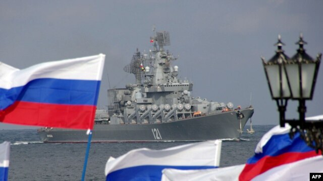 Russia supporters wave flags as a ship of Russia's Black Sea Fleet arrives in Crimea, Ukraine.