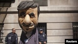 New York police officers look at a man dressed as President Mahmud Ahmadinejad during a protest against the Iranian leader outside the Warwick Hotel in New York.