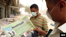 Iraqi men wearing surgical masks against a vicious sandstorm read an Iraqi paper with news of U.S. Vice President Joe Biden's visit on July 5.