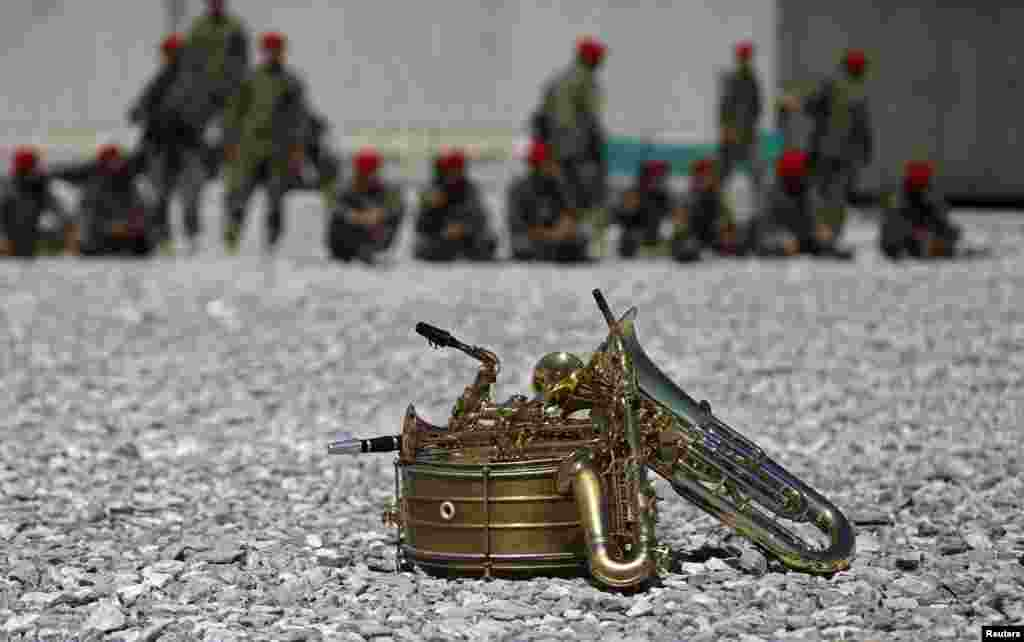 Musical instruments lie on the ground in front of members of the military during a ceremony to hand over the Bagram prison to Afghan authorities at the U.S. air base at Bagram. (Reuters/Mohammad Ismail)