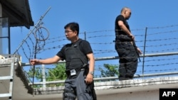 Philippines -- Heavily armed National Bureau of Investigation (NBI) agents patrol the perimeter fence of the prison building inside a police camp in Taguig City, suburban Manila on April 7, 2011, housing the suspects in the country's worst political massa