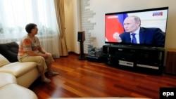 Женщина смотрит российский канал, в эфире которого транслируется выступление президента России Владимира Путина о ситуации в Украине. 4 марта 2014 года.