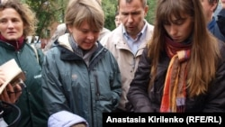 Yevgenia Chirikova (left, in green jacket) and fellow activist Ilona Zhuravleva show an aerial photo of the felling of Khimki Forest trees in late August.