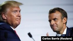 French President Emmanuel Macron and U.S. President Donald Trump react during a news conference at the end of the G7 summit in Biarritz, France, August 26, 2019
