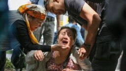 A Kazakh police officer (right) detains an opposition supporter in Almaty on June 10.