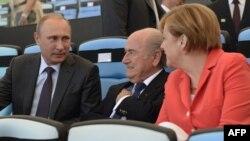Президент Росії Володимир Путін поруч із канцлером Німеччини Анґелою Меркель та президентом ФІФА Зеппом Блаттерем на стадіоні Маракана, Ріо–де–Жанейро, 13 липня 2014 року