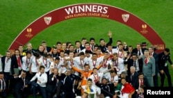 Italy -- Sevilla players and officials celebrate with the trophy after defeating Benfica in their Europa League final soccer match at the Juventus stadium in Turin, May 14, 2014