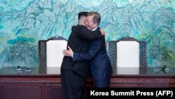 "North Korean leader Kim Jong Un (left) and South Korean President Moon Jae-in hug during a signing ceremony near the end of their historic summit in the truce village of Panmunjom on April 27. The leaders embraced warmly after signing a statement in which they declared ""there will be no more war on the Korean Peninsula."" (AFP/Korea Summit Press Pool)"