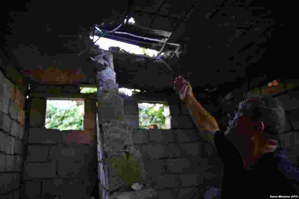 A man in the Armenian village of Aygepar points to his roof, which was damaged by shelling.