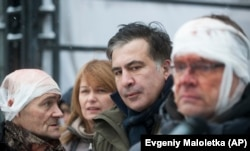 Former Georgian President Mikheil Saakashvili (center) speaks to people wounded during clashes with police in Kyiv on December 6.