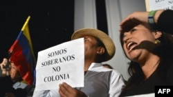 "Demonstrators hold a sign reading ""We are sovereign, not colonies,"" as they shout slogans outside the British Embassy in Quito on August 15."