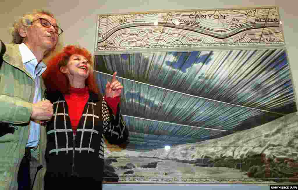Christo and his wife, Jeanne-Claude, discuss a drawing for their work titled Over the River: Project For The Arkansas River, Colorado, in January 2002 at the National Gallery in Washington, D.C.