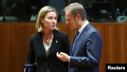 EU foreign policy chief Federica Mogherini (left) talks to European Council President Donald Tusk in Brussels on December 18.