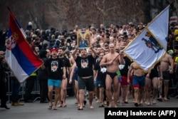 Сербские православные верующие идут на традиционное крещенское купание в футболках с изображением Владимира Путина