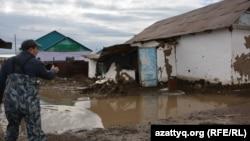 Человек у разваливающегося после паводков дома в селе Махамбет. Актюбинская область, 18 апреля 2017 года.