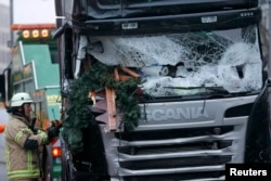 A firefighter stands beside a truck that plowed through a crowded Christmas market in Berlin. At least 12 people were killed.
