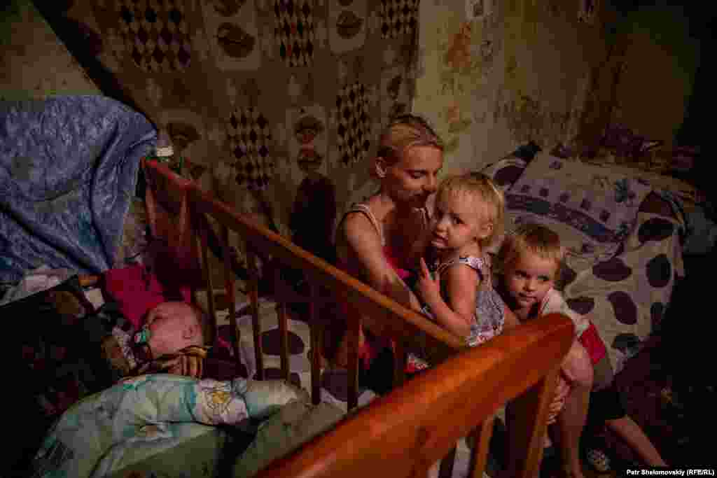 Svetlana sits with her three children. The youngest is less than a year old.