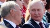 Президент России Владимир Путин смотрит на бывшего президента Нурсултана Назарбаева, прибывшего в Москву и участвующего в торжествах по случаю Дня города. Сентябрь 2019 года