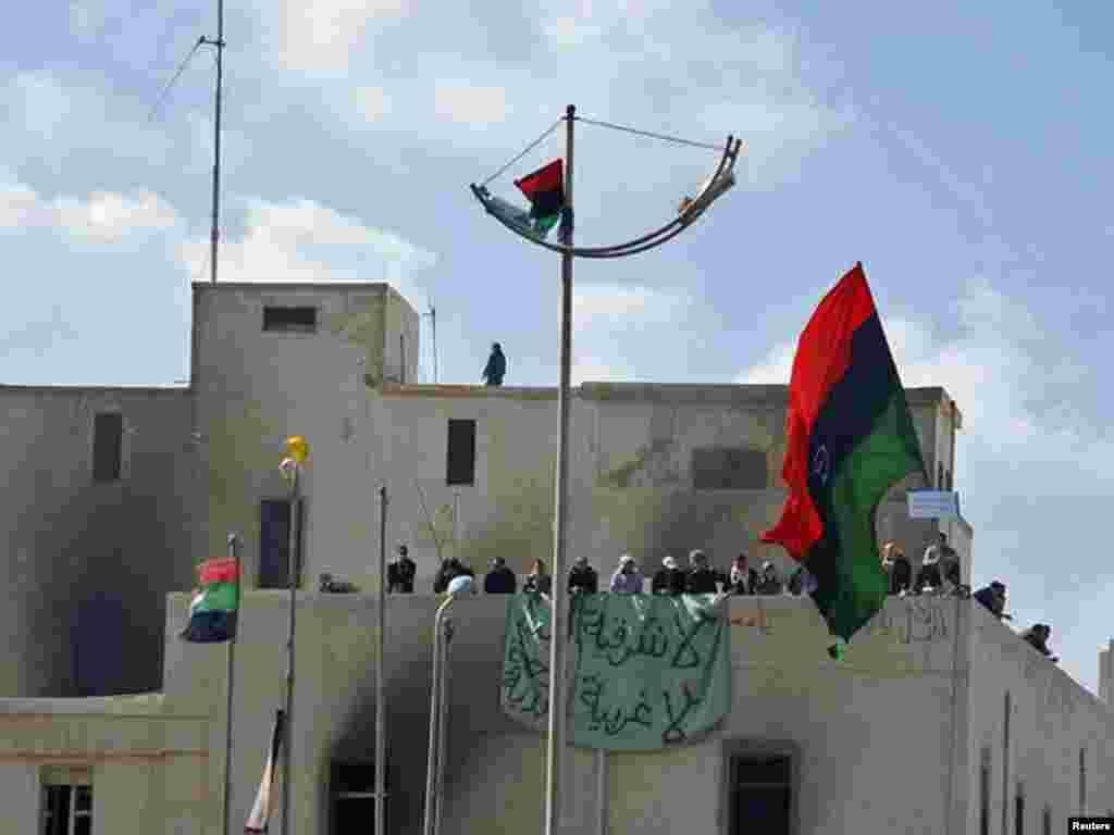 تظاهرکنندگان در حال تکان دادن پرچم ها بر بام ساختمان سوخته شده در بنغازی