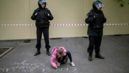 "A young girl writes ""I'm for the park"" on the asphalt in front of a fence designed to block demonstrators protesting plans to construct a cathedral in a park in Yekaterinburg on May 16."