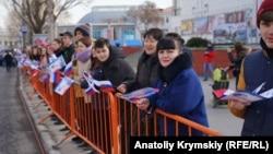 Симферопольцы за ограждением наблюдают за ходом шествия по случаю пятилетней годовщины аннексии Крыма. 15 марта 2019 года