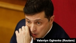 Ukrainian President Volodymyr Zelenskiy reacts during a parliamentary session in Kyiv on March 4, which ushered in a major cabinet reshuffle.