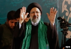 Iranian conservative presidential candidate Ebrahim Raisi waves to supporters on the campaign trail.