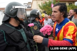 A pro-Catalonia supporter offers a flower to a policeman.