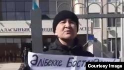 Активист гражданского общества Макс Бокаев протестует перед зданием управления полиции Атырау. 13 марта 2021 года.