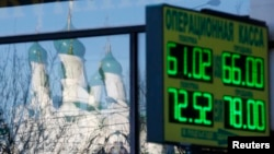 A board showing currency-exchange rates is on display in a street, with a church reflected in a shop window in Moscow on January 6.