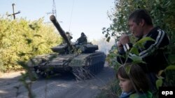 Местные люди смотрят на танк пророссийских сепаратистов на востоке Украины. 3 октября 2015 года.