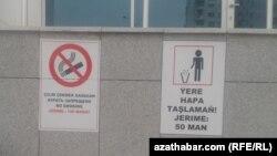 Плакат с предупреждениями о запрете курения (слева) на стене административного здания в Ашгабате.