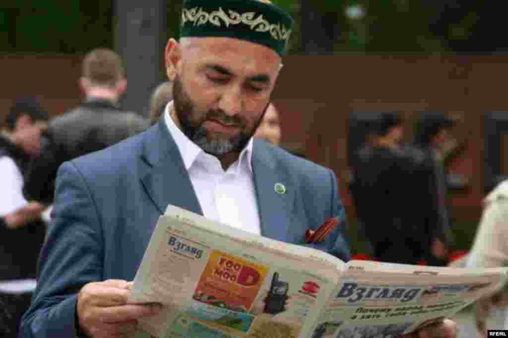 28 панфиловшылар саябағында «Алға» партиясының белсенділері таратқан газетті оқып тұрған адам. Алматы, 1 мамыр 2010 жыл.