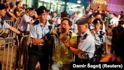 Гонконг полициясы Қытай төрағасы Си Цзиньпиннің сапарынан бір күн бұрын өткен наразылық акциясына қатысушыны ұстап әкетіп барады. 28 маусым 2017 жыл.