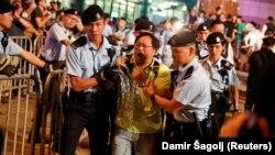 Полицейские ведут задержанного участника протестов, устроенных за день до визита президента Китая Си Цзиньпина. Гонконг, 28 июня 2017 года.