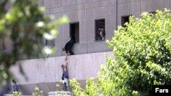 Чоловік допомагає спустити дитину з будівлі парламенту Ірану через вікно, Тегеран, 7 червня 2017 року