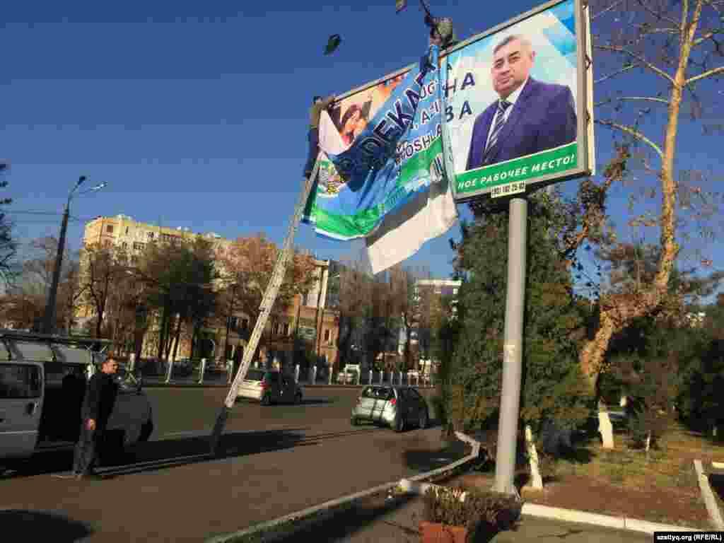 Билборд с изображением кандидата Хотамжона Кетмонова меняют на билборд ко Дню Конституции, который отмечается в Узбекистане 8 декабря.