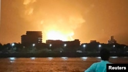 "A man watches Indian Navy submarine ""INS Sindhurakshak"" on fire in Mumbai late on August 13."