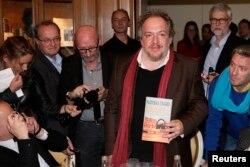 Маціяс Энар трымае сваю кнігу «Компас» у парыскім рэстаране «Drouant» 3 лістапада 2015 году
