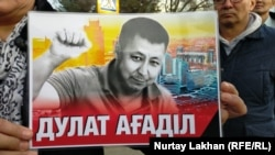 Портрет Дулата Агадила в руках собравшихся в Алматы людей, которые потребовали объективного расследования обстоятельств смерти активиста в СИЗО. 26 февраля 2020 года.