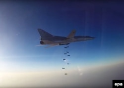 A still image taken from video footage released by Russia's Defense Ministry shows a Russian Tupolev Tu-22M3 long-range bomber based in Iran dropping off bombs at an unknown location in Syria.